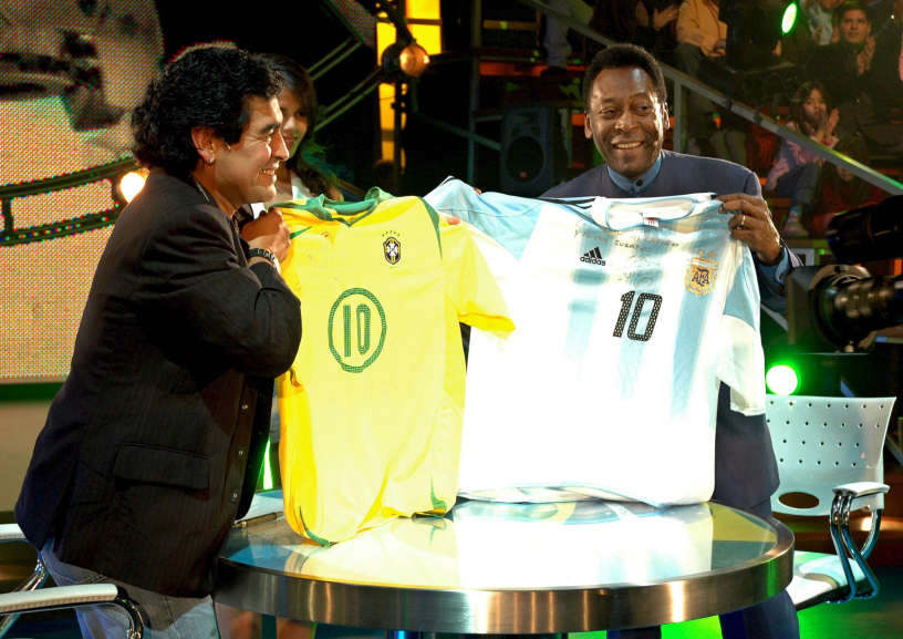 Argentinean former soccer star, Diego Maradona (L), holding a Brazilian national soccer team jersey as his Brazilian counterpart, Pele, displays an Argentinian one